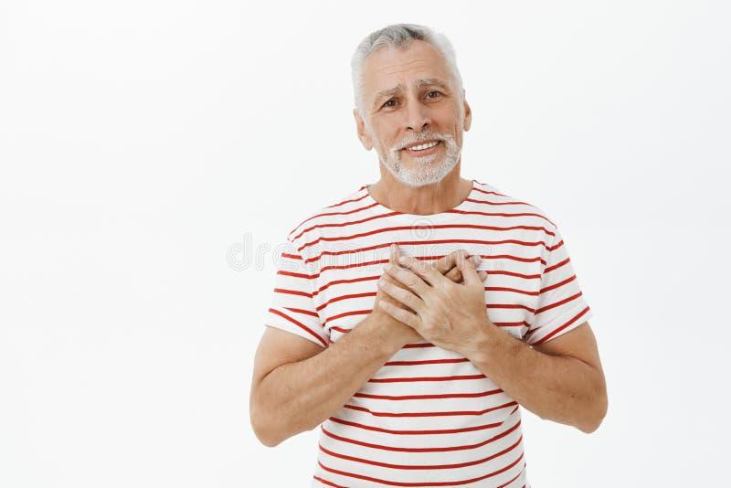 高兴和感恩的逗人喜爱的成熟祖父感觉画象象熔化从恳切的幸福藏品的心脏的 免版税库存照片