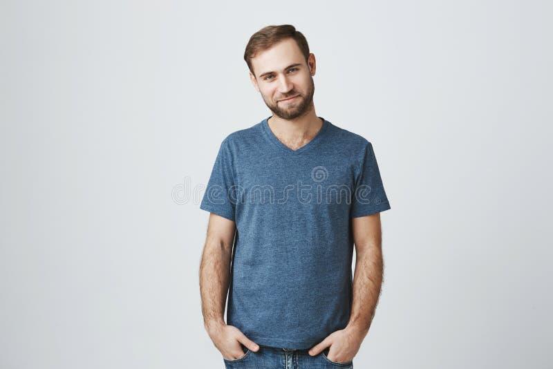 高兴有胡子年轻男性愉快有与女朋友的日期,在好心情,穿戴随便,被隔绝反对灰色 免版税库存照片
