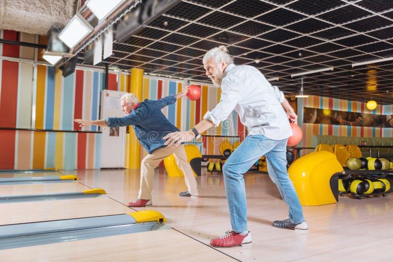 高兴正面演奏一起滚保龄球的年迈的人 免版税图库摄影
