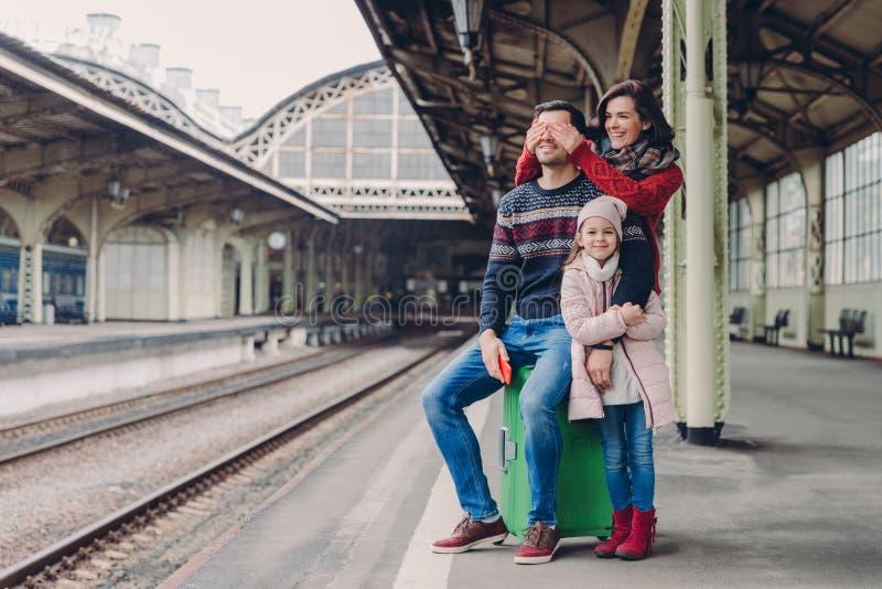 高兴的女性盖她的丈夫的眼睛,做惊奇 一起母亲、父亲和女儿立场友好的家庭在铁路 免版税库存图片