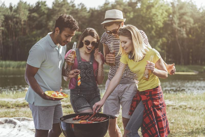 高兴的年轻公司烧烤啤酒快餐在森林里 图库摄影