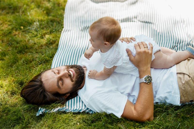 高兴的年轻父亲放置与一点迷人的女儿在镶边床罩在草 有结婚戒指 免版税库存图片
