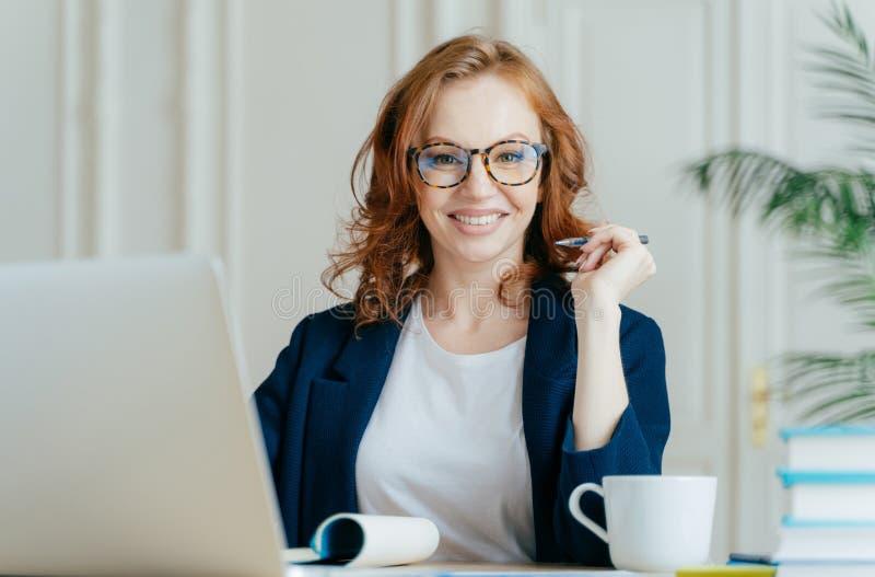 高兴的红头发人卷曲妇女在笔记薄工作自由职业者,使用手提电脑,写下笔记,喝咖啡,佩带光学玻璃 库存照片