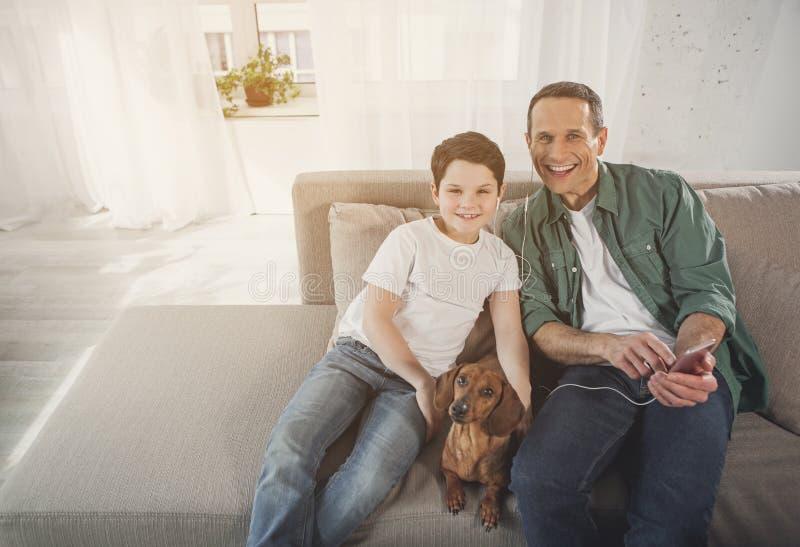 高兴的花费时间的父母和男孩在有小狗的沙发上 库存照片