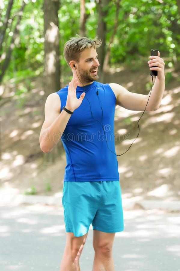 高兴看您 在跑前的运动员手机录影电话 人运动员微笑的面孔网上训练看见教练 库存照片
