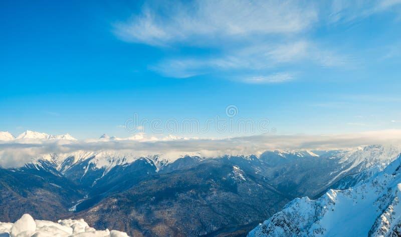 高加索山脉美丽的多雪的土坎在清楚的天空蔚蓝下的在Krasnaya Polyana,俄罗斯 库存图片