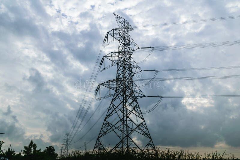 高压力量定向塔和阴云密布 免版税库存照片