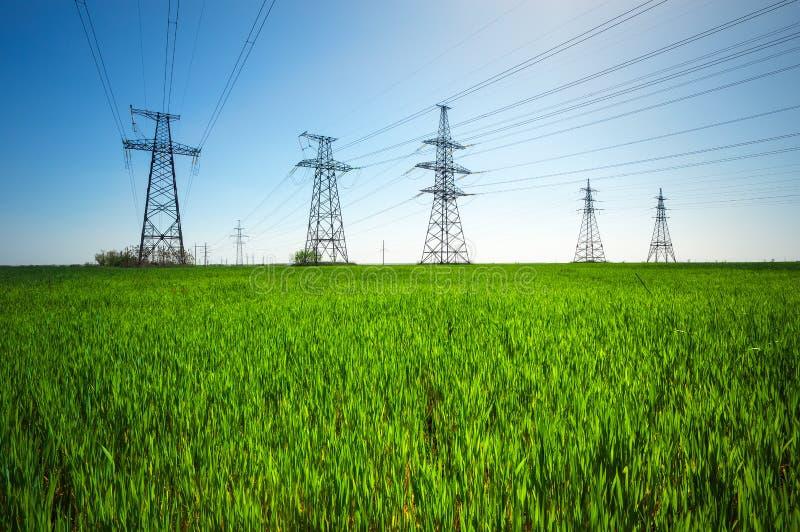 高压线和力量定向塔和绿色领域 免版税库存图片