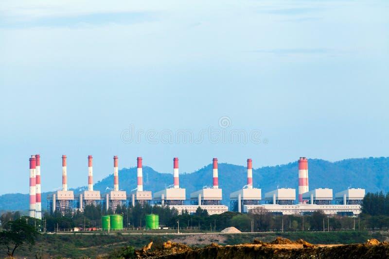 高压线和力量定向塔在一个平和绿色农业风景与触毛 免版税库存照片