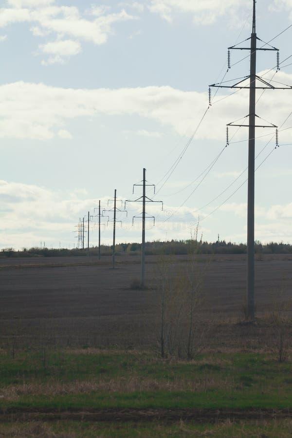 高压线和力量定向塔在夏天调遣 库存照片