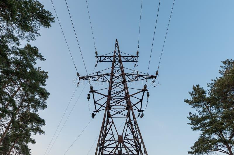 高压线和次幂定向塔 附近蓝天和林木 免版税库存照片
