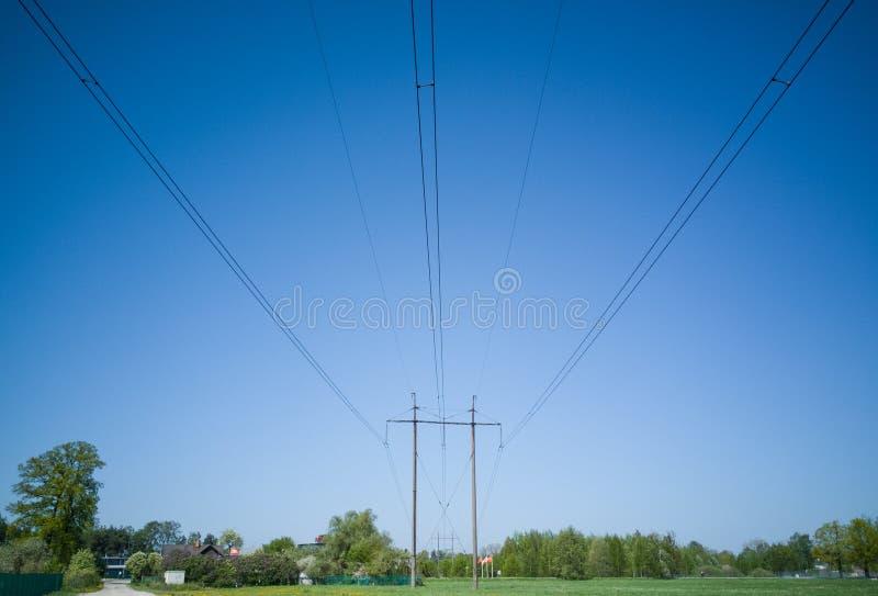 高压输电线去在草甸在村庄 免版税图库摄影