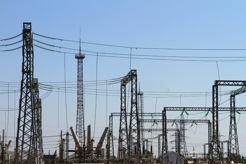高压输电线和天空蔚蓝定向塔  电力分站 库存照片