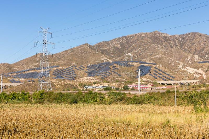 高压输电线和太阳电池板在山,中国 库存照片