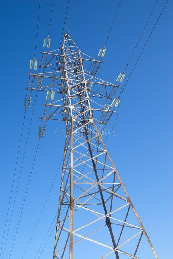 高压输电线在蓝天的金属支柱 免版税库存照片