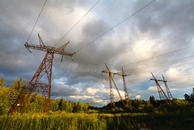 高压输电线 在日落的电发行 喂 免版税库存图片