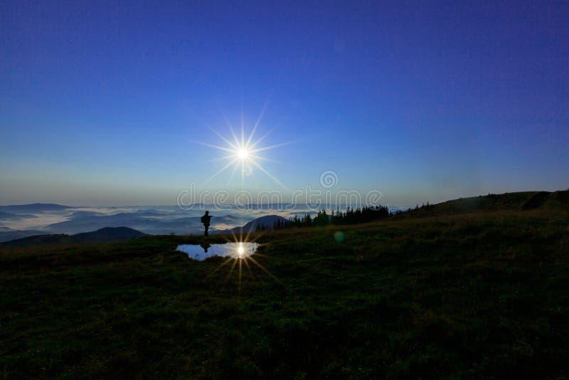 高在云彩上的山年轻人寻找拿着他的电话的多孔的连接高 库存图片