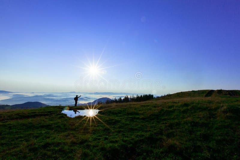 高在云彩上的山年轻人寻找拿着他的电话的多孔的连接高 免版税库存照片
