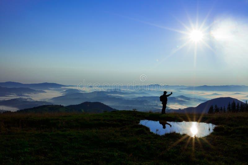 高在云彩上的山年轻人寻找拿着他的电话的多孔的连接高 免版税库存图片