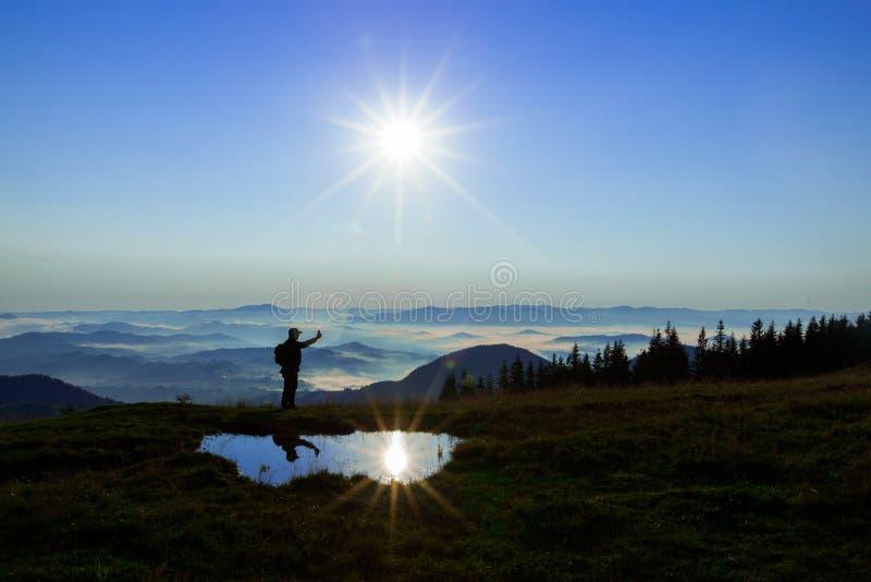 高在云彩上的山年轻人寻找拿着他的电话的多孔的连接高 免版税图库摄影
