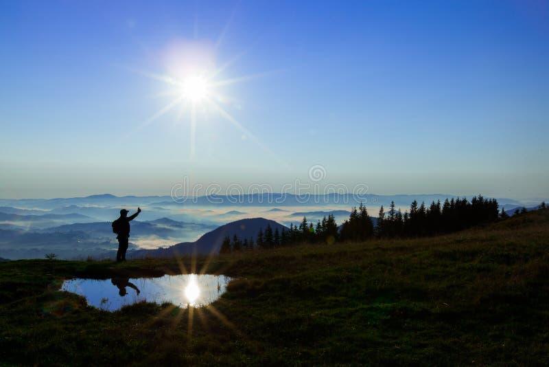 高在云彩上的山年轻人寻找拿着他的电话的多孔的连接高 图库摄影