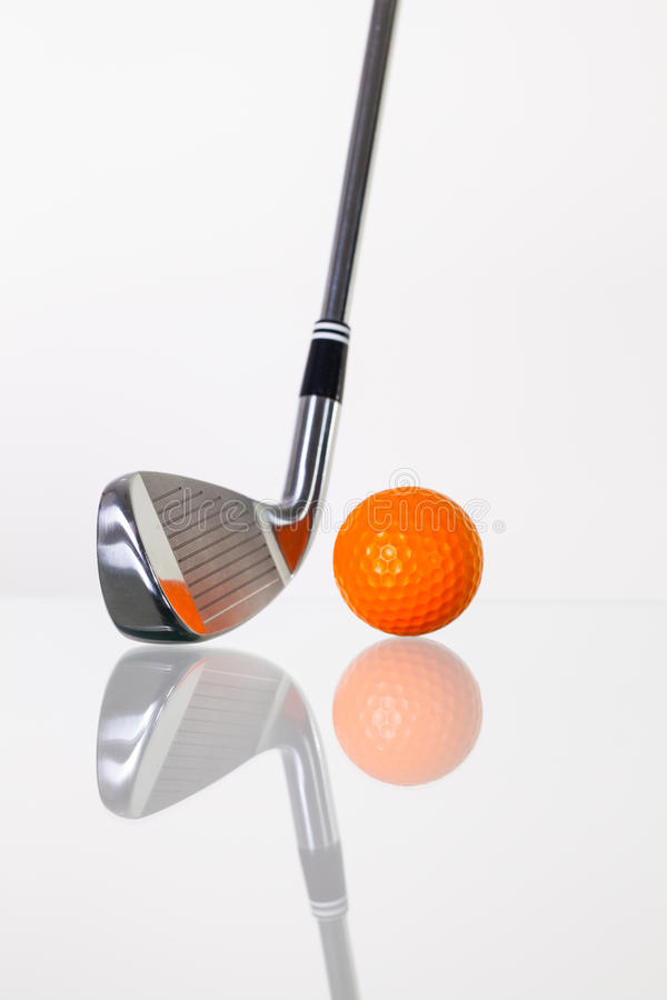 高尔夫俱乐部和高尔夫球在玻璃书桌上 免版税库存图片