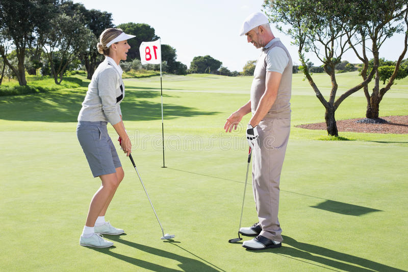 高尔夫球区的夫人高尔夫球运动员在与伙伴的第十八个孔 免版税图库摄影