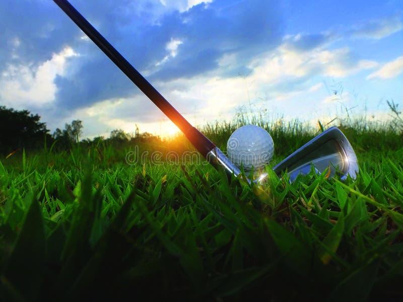 高尔夫球和铁 在绿色草坪击中高尔夫球场 特写镜头高尔夫球在柔和绿色草坪,当暴露在阳光体育p 库存图片
