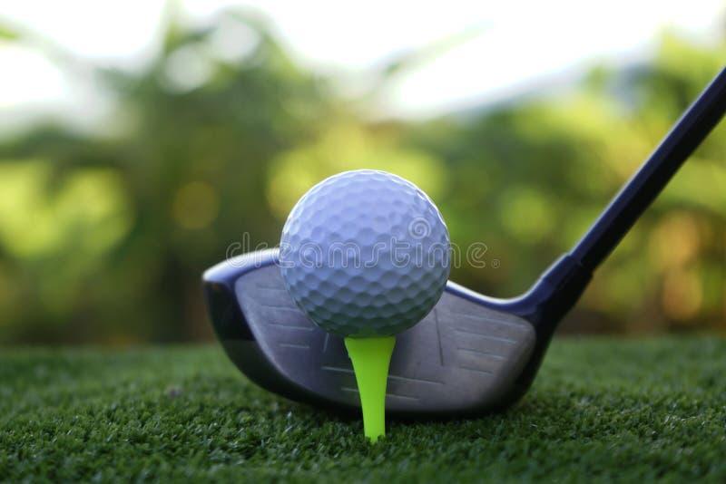 高尔夫球和高尔夫俱乐部在日落backg的美好的高尔夫球场 免版税库存图片