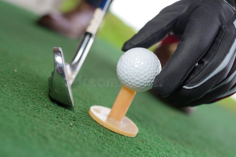 高尔夫球在黄色发球区域的手手套 免版税库存照片