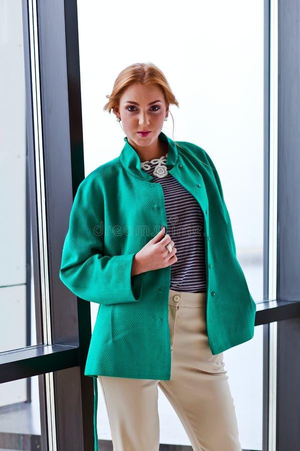 高尔夫球外套的年轻美丽的妇女 免版税库存图片