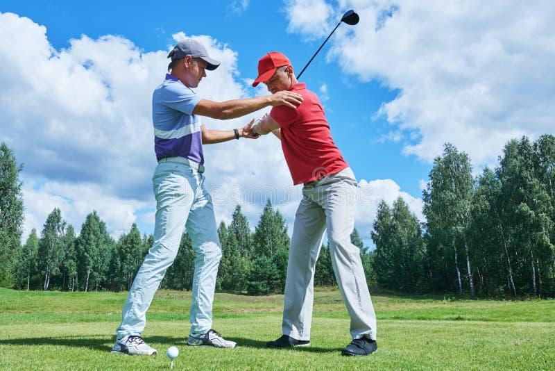 高尔夫球训练 辅导员在夏天训练新的球员 免版税图库摄影