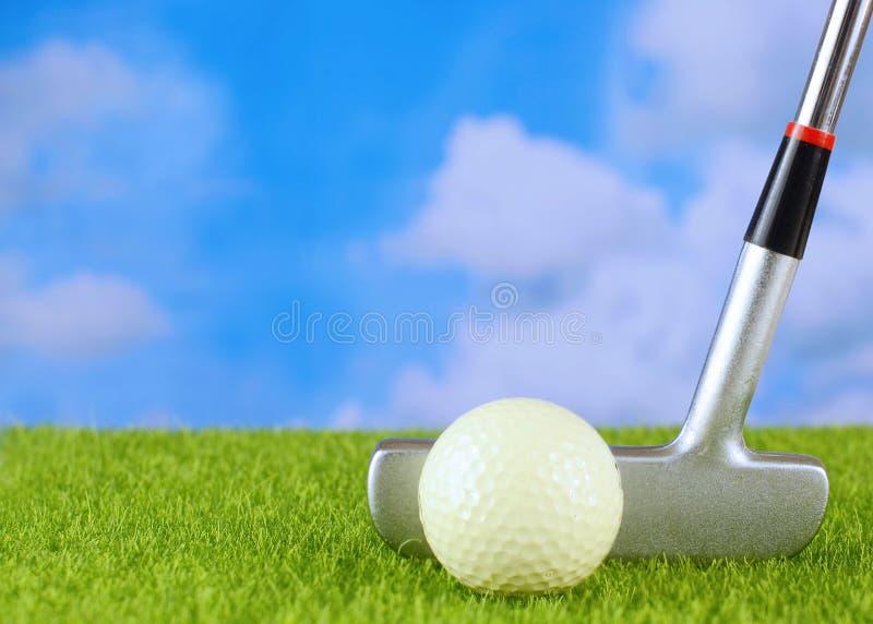 高尔夫球轻击棒和球在虚假草 天空蔚蓝有松的白色云彩背景 免版税库存照片