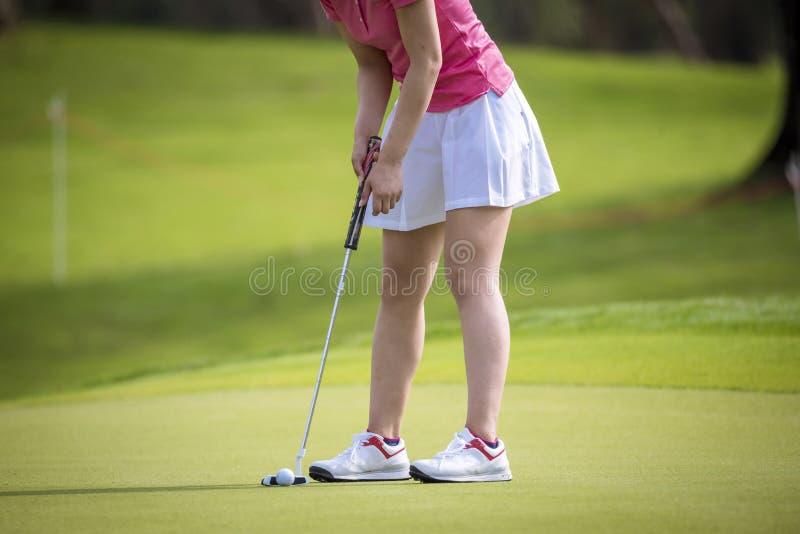 高尔夫球运动员由从发球区域箱子的高尔夫俱乐部推挤高尔夫球在竞争比赛的高尔夫球场 库存照片