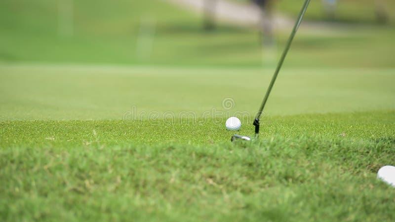 高尔夫球运动员由从发球区域箱子的高尔夫俱乐部推挤高尔夫球在竞争比赛的高尔夫球场 免版税库存图片