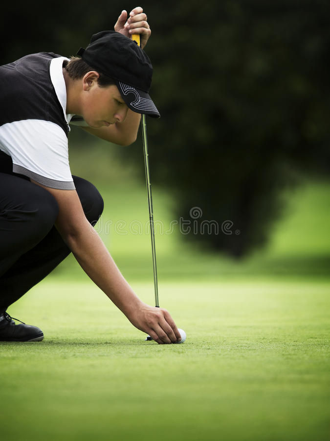 高尔夫球运动员绿色男性squating 免版税库存图片