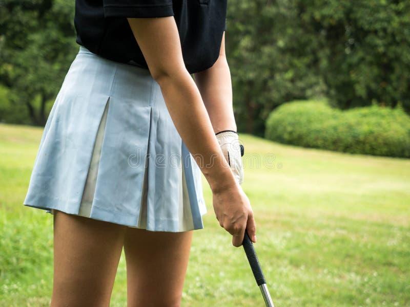 高尔夫球运动员高尔夫球的妇女发球区域在摇摆前 免版税图库摄影