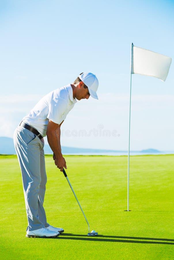 高尔夫球运动员绿色放置 库存照片