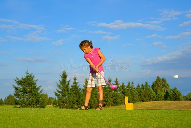 高尔夫球,击中球的女孩高尔夫球运动员 免版税库存照片