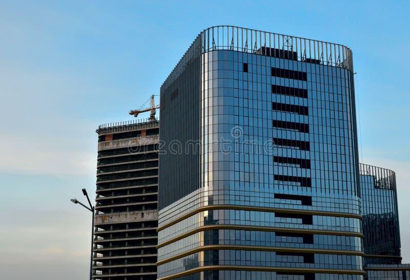 高层建筑物建设中与运转在天空的背景的起重机 编译的多楼层 建筑  免版税库存图片