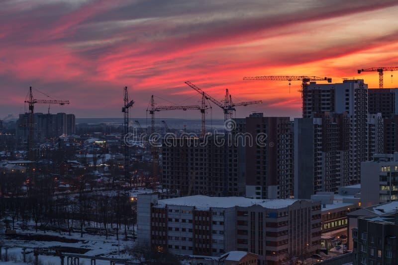 高层建筑物绯红色日落天空背景的建造场所 沃罗涅日,俄罗斯 库存图片