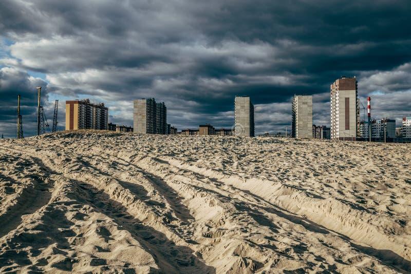 高层未完成的房子在沙漠沙子的背景中 免版税库存图片