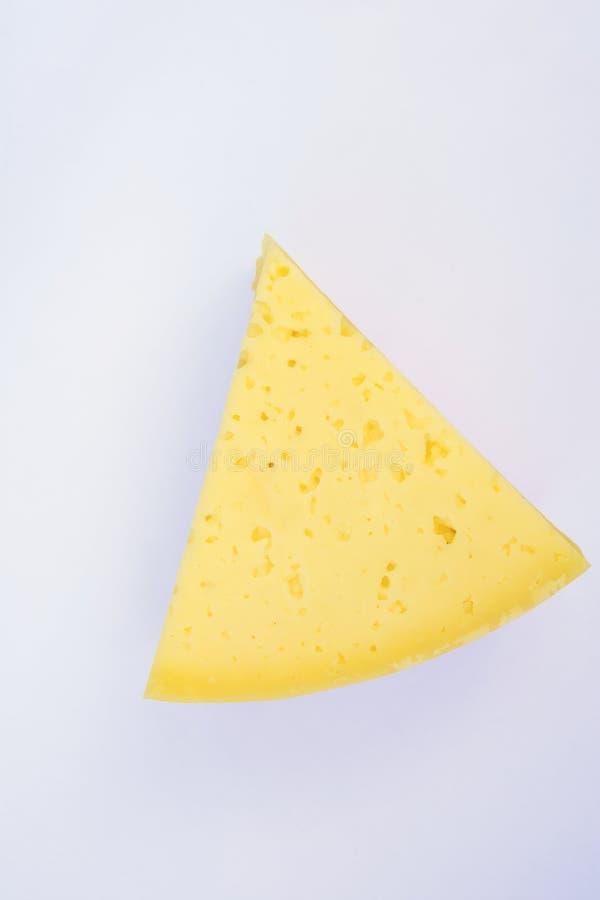 高山乳脂状的开胃淡黄色太尔西特干酪乳酪三角大块楔子在白色背景的 与镇压和孔的纹理 库存照片