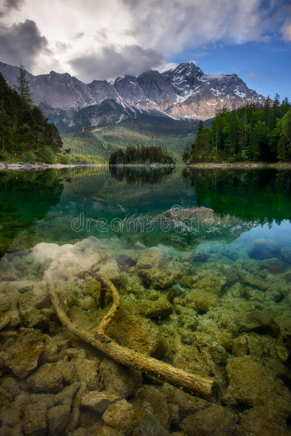 高山峰顶楚格峰的美好的反射在Eibsee湖和令人惊讶的风雨如磐的云彩,巴伐利亚,德国的 图库摄影