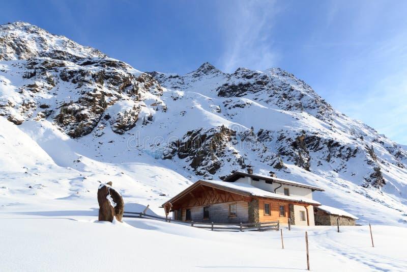 高山瑞士山中的牧人小屋房子和山全景有雪的在冬天在Stubai阿尔卑斯 免版税库存图片