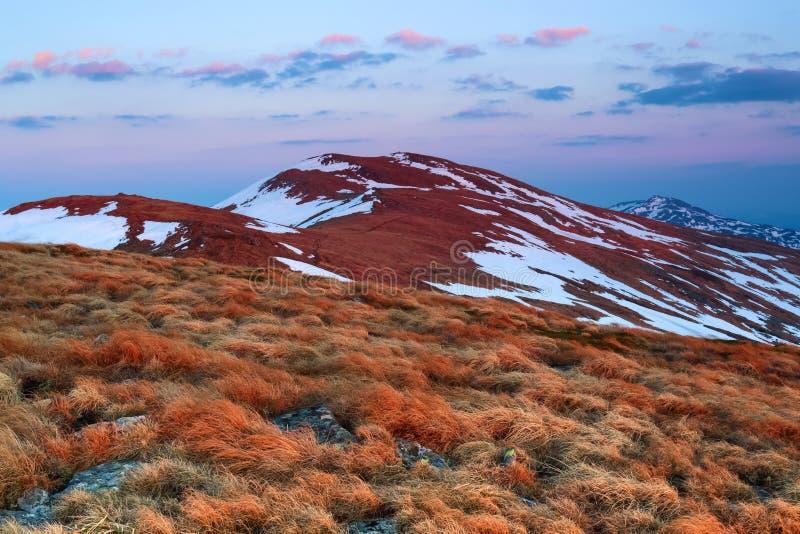 高山的风景在雪的 草和岩石在草甸 日出照亮天际 天空 库存照片