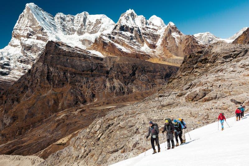 高山登山人合作继续前进冰川高山视图背景 免版税库存图片