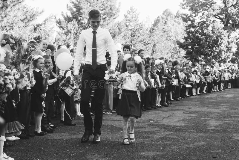 高年级的学生和有响铃的一个女孩一年级学生在一条学校庄严的线的手上在天知识,染黑a 库存图片