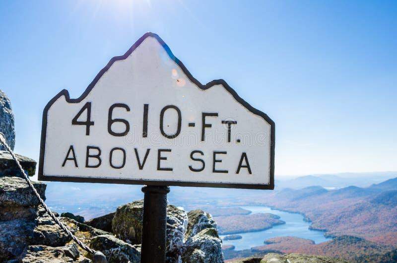 高度标志在反对清楚的天空的一座山顶部 免版税库存图片