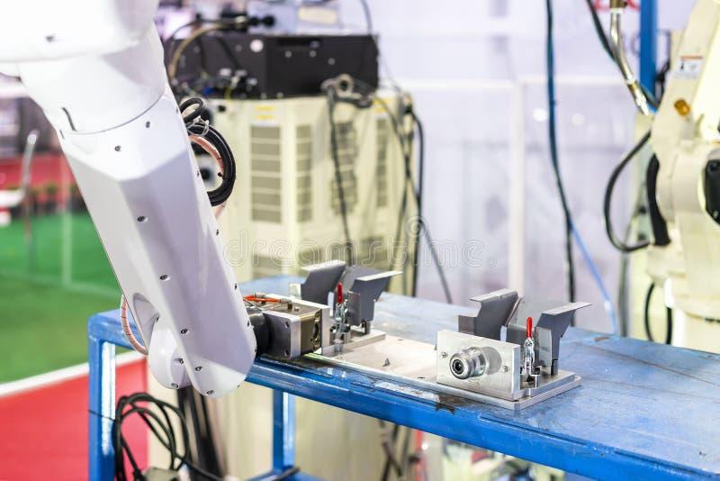 高技术和精确度与自动快的锁钳位的机器人抓住产品在夹具设定的工作片断的夹子或牛颈肉 免版税库存图片